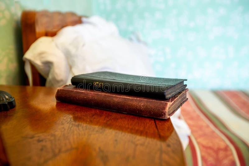 Livre fermé sur la table de chevet en bois près du lit chiffonné images libres de droits