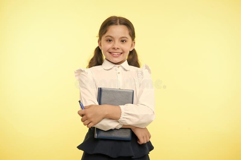 Livre heureux de prise d'écolière sur le fond jaune Sourire de petite fille avec le manuel et le stylo Sûr dans sa connaissance images libres de droits