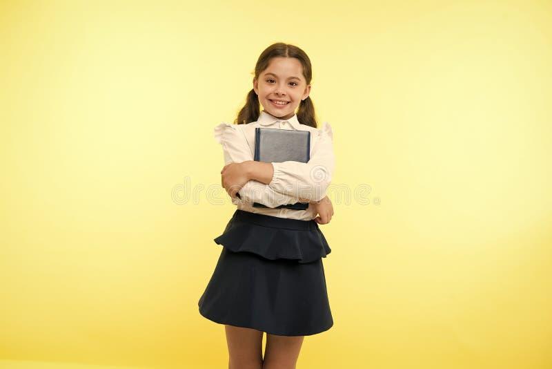 Livre heureux de prise de fille sur le fond jaune Petit sourire d'écolière avec le manuel Rat de bibliothèque de mode Premier jou images libres de droits