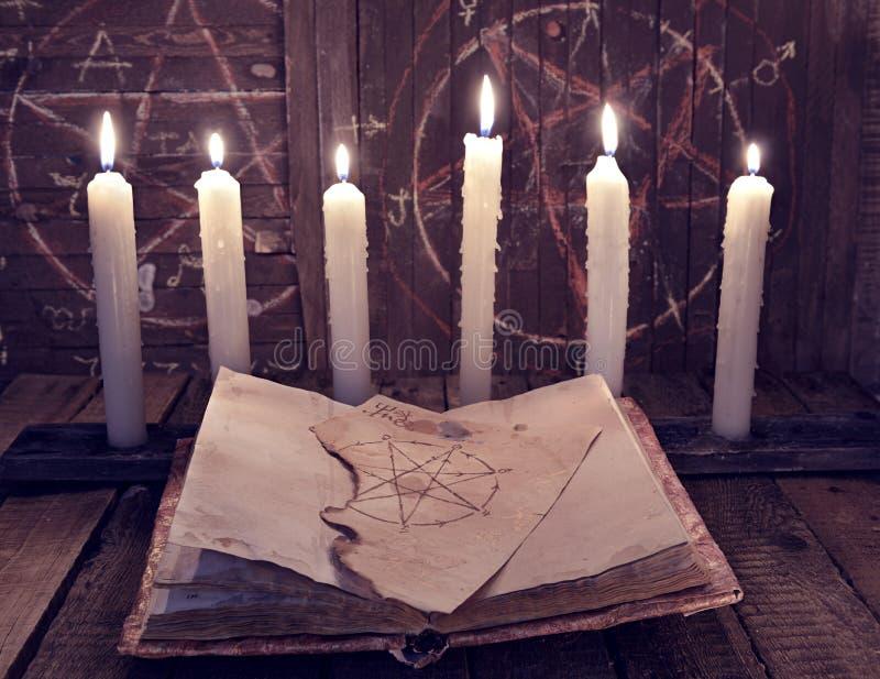 Livre magique avec des bougies de pentagone étoilé et de mal pour le rituel occulte image stock