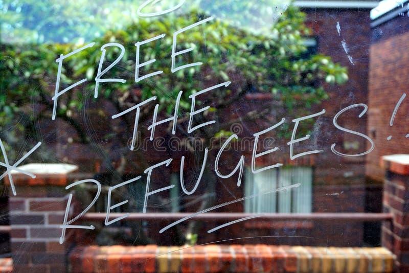 Livre os refugiados, grafittis no abrigo de ônibus de vidro foto de stock royalty free