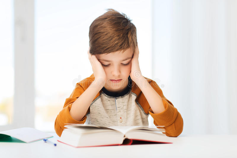 Livre ou manuel de lecture de garçon d'étudiant à la maison photographie stock