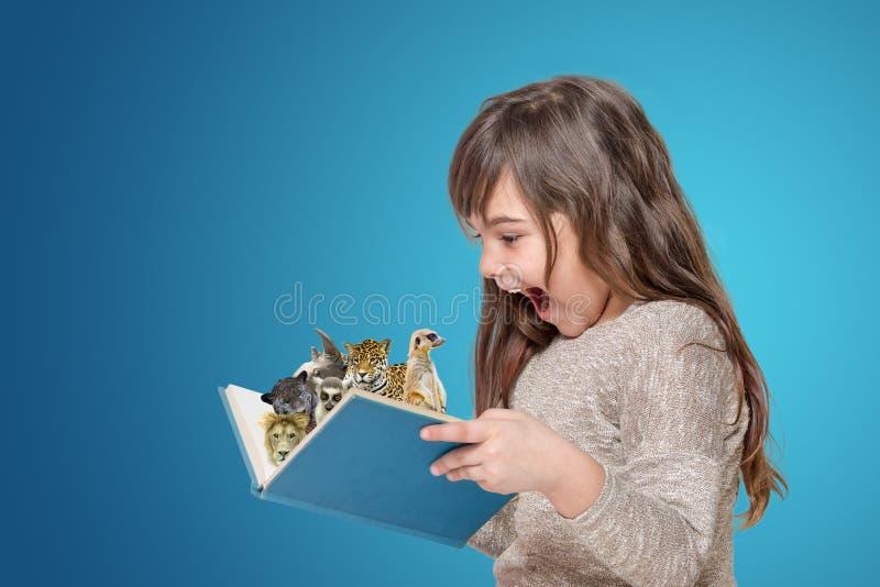 Livre ouvert étonné de participation de petite fille avec des animaux images stock