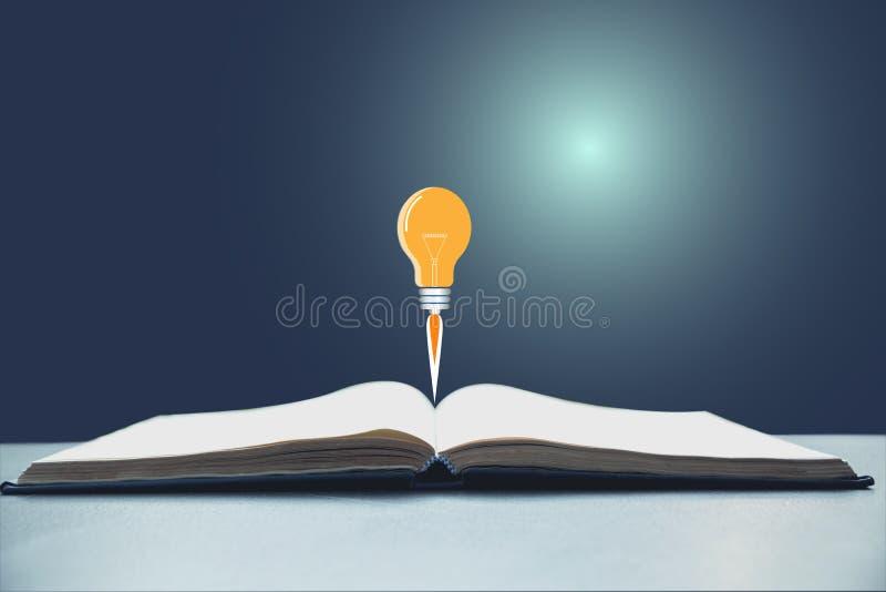 Livre ouvert avec le lancement d'ampoule Livre ouvert sur le bureau image libre de droits