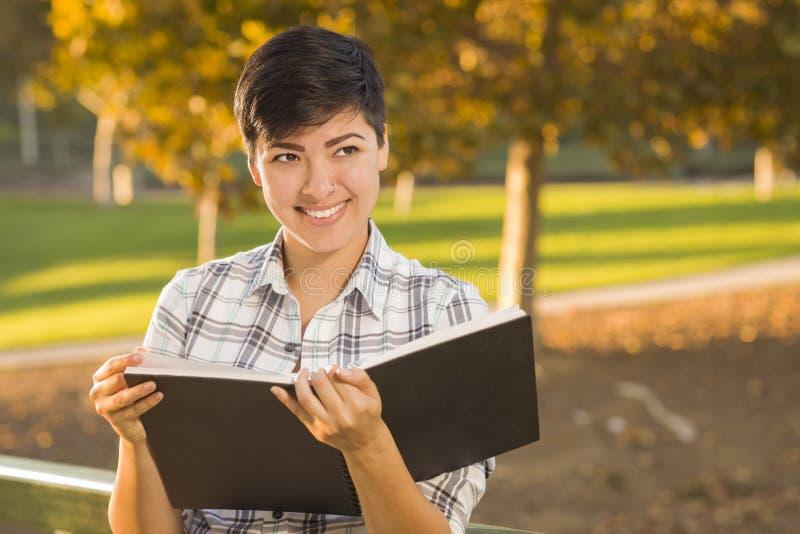 Livre ouvert et crayon de jeune participation femelle de métis dehors images libres de droits