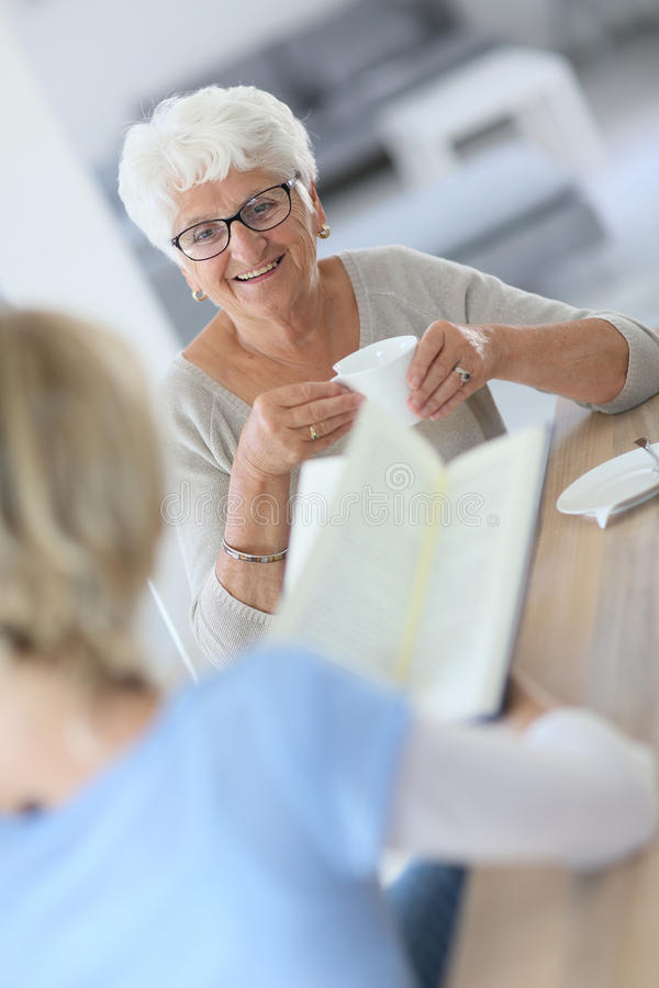 Livre reaading de soignant à la maison à la femme agée photographie stock libre de droits