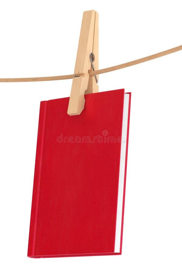 Livre rouge accrochant sur une corde par la pince à linge image stock