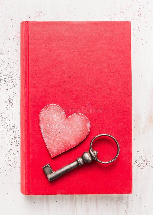 Livre rouge de journal intime avec la clé de coeur et de vintage sur le fond en bois blanc, vue supérieure Carte de jour de Valen photographie stock