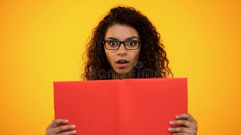 Livre rouge de participation millénaire femelle futée d'Africain choqué avec des faits scientifiques photos stock