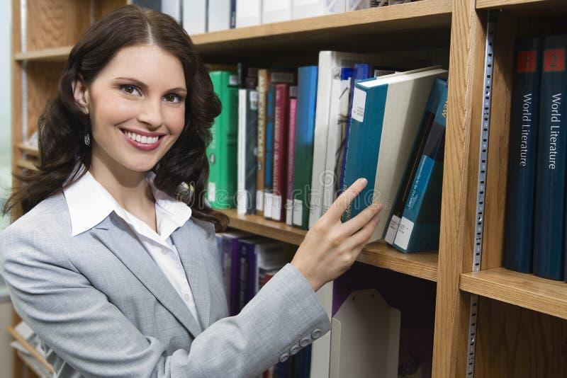 Livre sélectionnant femelle d'étagère images stock