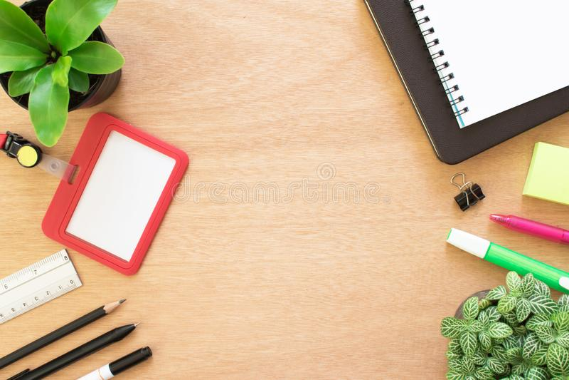 Livre, trombone, crayon, règle, accentuant le stylo, la carte des employés, le post-it et le pot d'arbre sur le bureau en bois br images stock