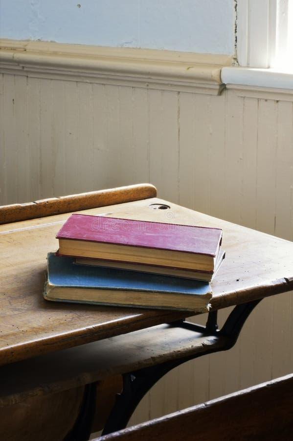 Livres antiques empilés sur la lumière excessive de bureau d'école photographie stock libre de droits