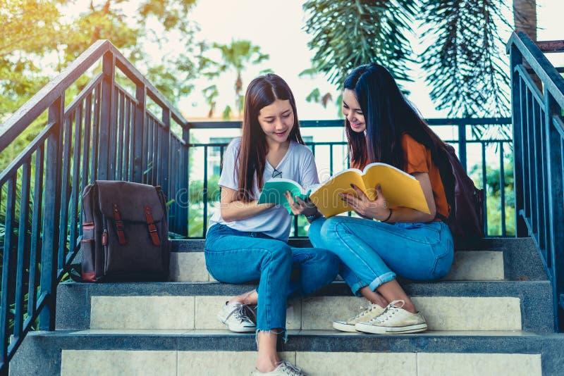 Livres asiatiques de lecture et de soutien scolaire de deux filles de beauté pour l'examen final ensemble ?tudiant souriant et s' image stock