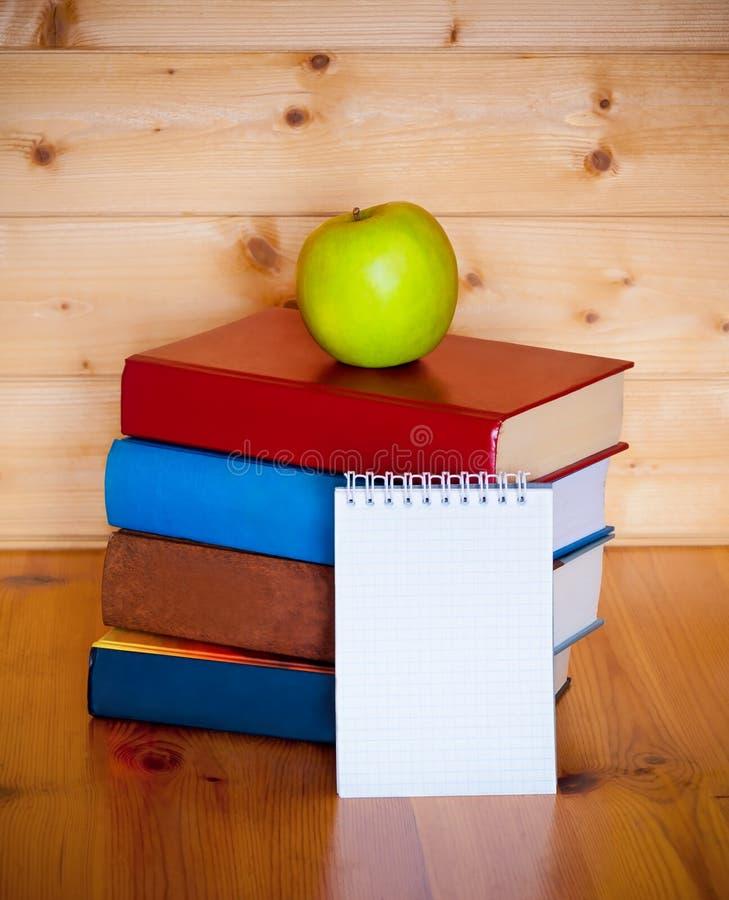 Livres, bloc-notes et pomme sur la table en bois au-dessus du fond en bois photo stock