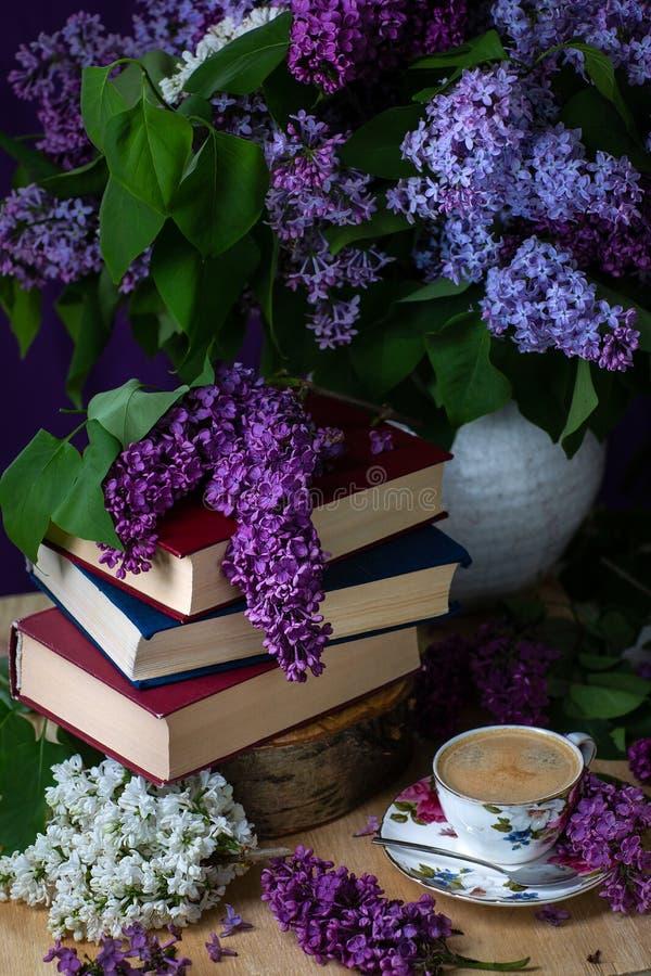 Livres, café et lilas toujours de la vie dans la clé foncée Fond de source image stock