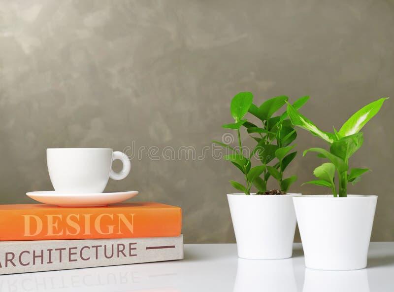 Livres, café et plantes sur le bureau image stock