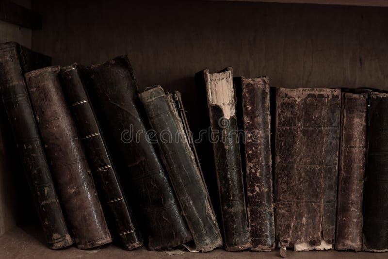Livres d'antiquité sur l'étagère Livres attachés de vintage de vieux cuir photographie stock