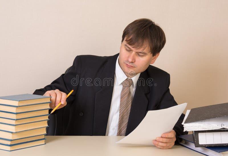 Livres de comptes des employés avec des documents à la table dans le bureau photos stock