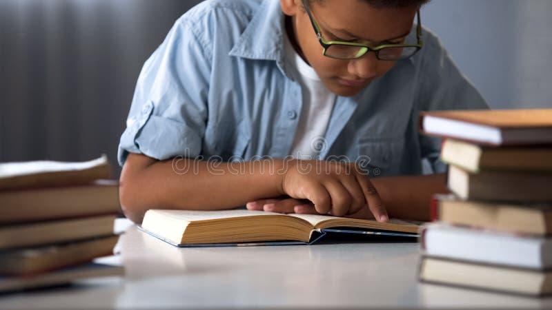 Livres de lecture afro-américains futés de garçon, enfant de rat de bibliothèque, petit ballot, éducation images libres de droits