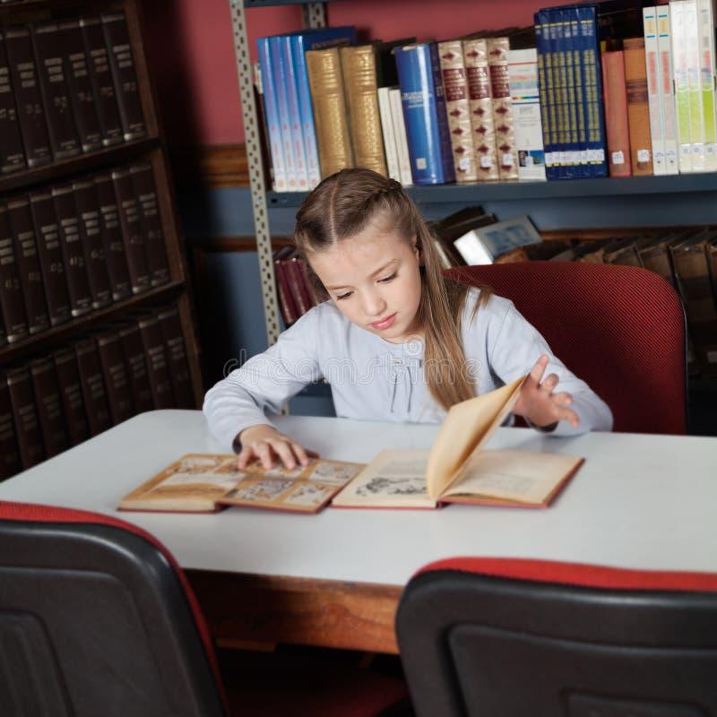 Livres de lecture d'écolière au Tableau photographie stock