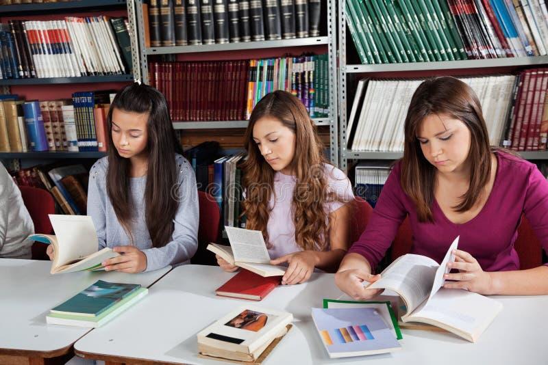 Livres de lecture d'écolières dans la bibliothèque images stock
