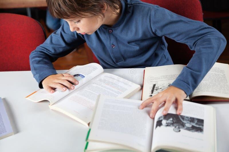 Livres de lecture d'écolier dans la bibliothèque images stock