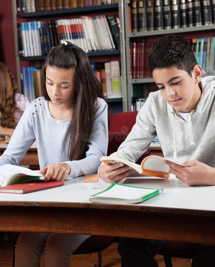Livres de lecture d'écoliers dans la bibliothèque photo libre de droits