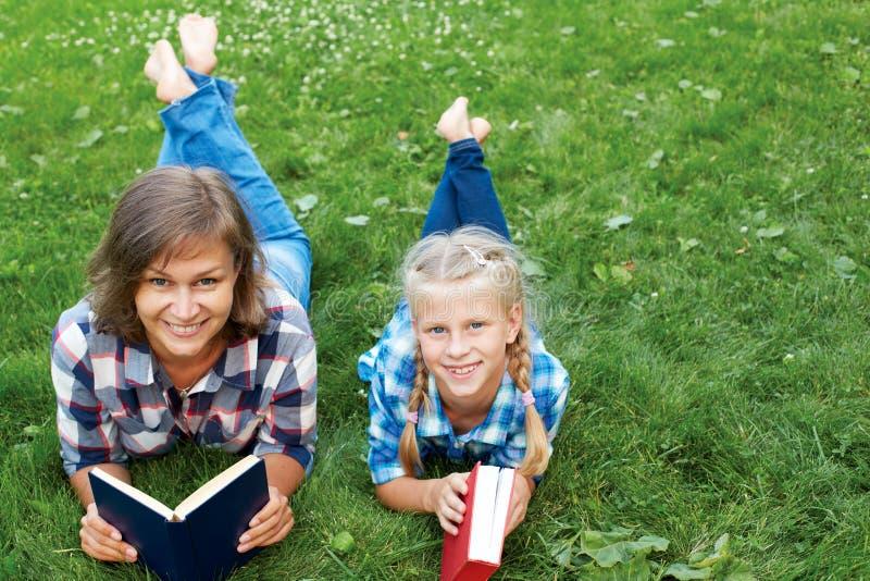 Livres de lecture de parent et d'enfant ensemble en parc images stock