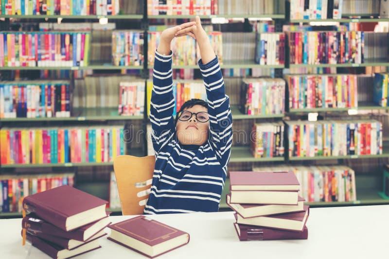 Livres de lecture de gar?on de l'Asie d'enfants pour l'?ducation et aller instruire dans la biblioth?que images libres de droits