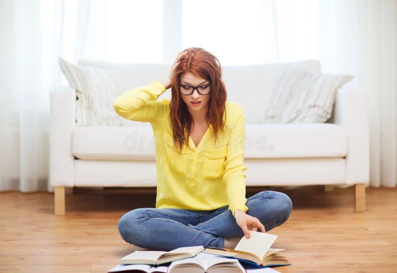 Livres de lecture soumis à une contrainte de fille d'étudiant à la maison image stock