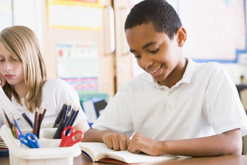 Livres de relevé d'écoliers dans la classe image libre de droits