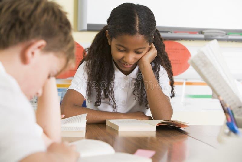 Livres de relevé d'écoliers dans la classe images libres de droits