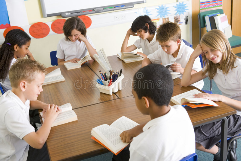 Livres de relevé d'écoliers dans la classe photos libres de droits