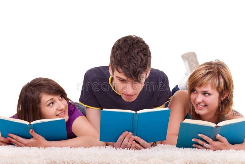 Livres de relevé d'adolescents sur l'étage photographie stock