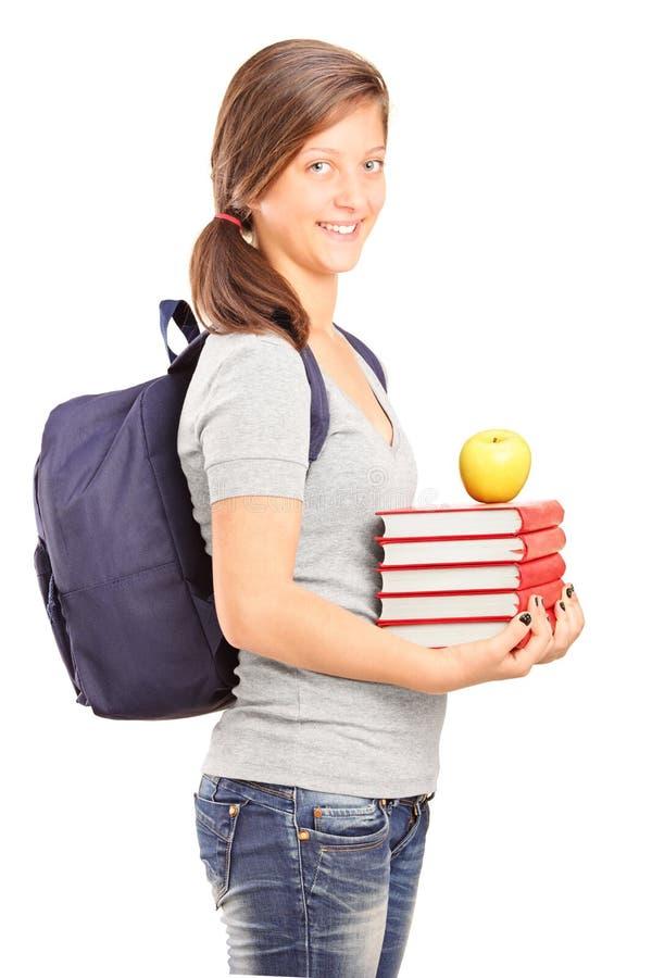 Livres de sourire d'une exploitation d'écolière et pomme verte photos stock
