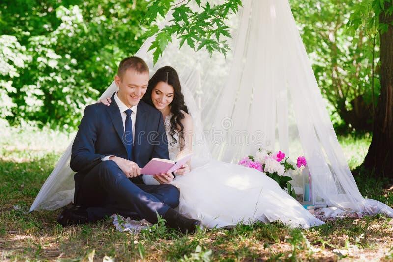 Livres dehors de sourire de caresse et de lecture de jeunes mariés, décor, pivoines, fleurs, mode de vie, mariage, famille, amour photo libre de droits
