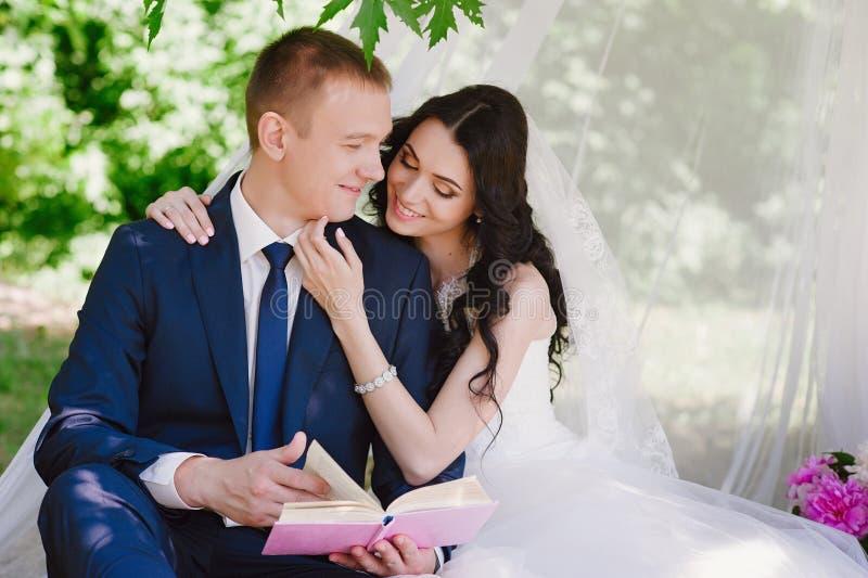 Livres dehors de sourire de caresse et de lecture de jeunes mariés, décor, pivoines, fleurs, mode de vie, mariage, famille, amour photographie stock libre de droits