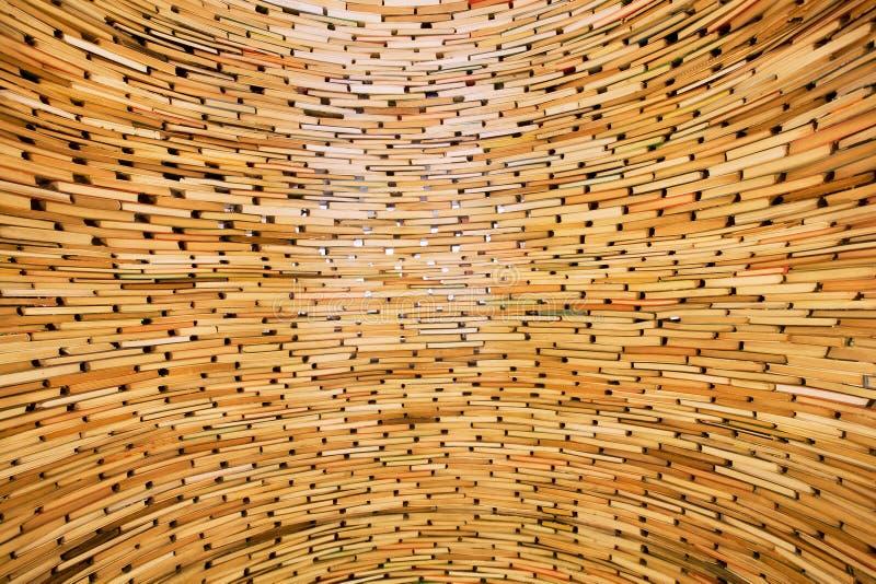 Livres empilés dans les couches dans le mur énorme de la connaissance images stock