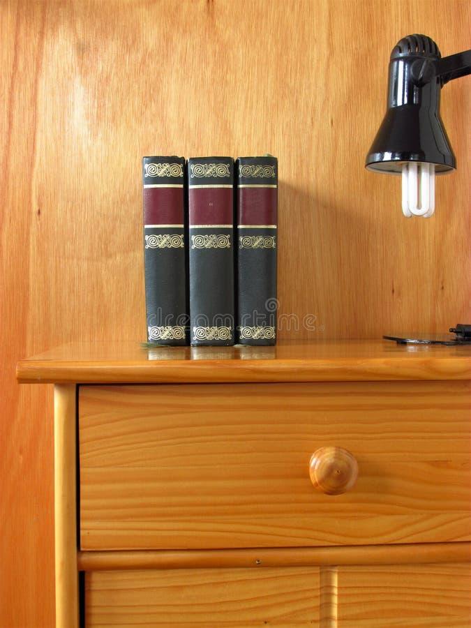 Livres et lampe de bureau sur le nightstand avec le tiroir photos libres de droits