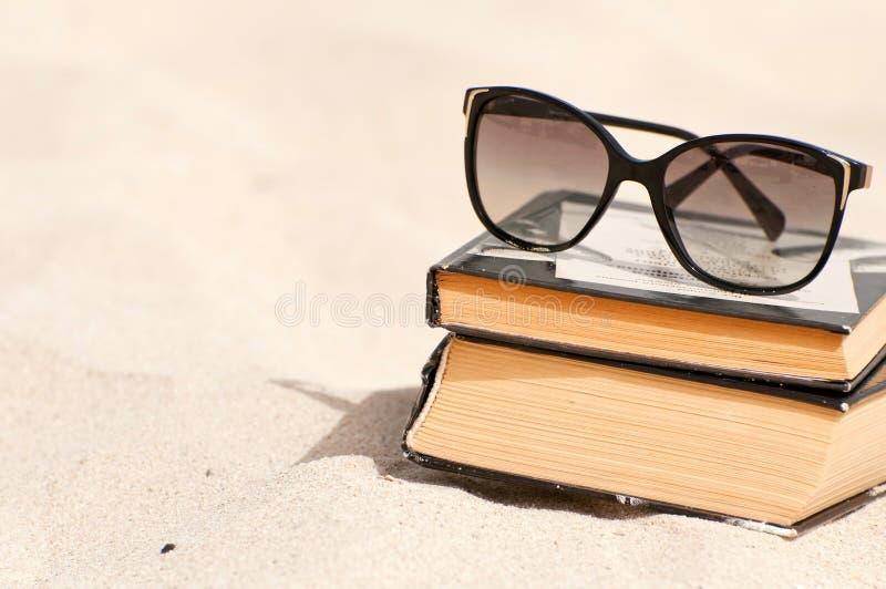 Livres et lunettes de soleil sur une plage images libres de droits