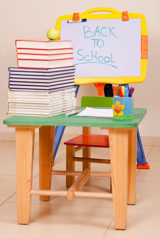 Livres et pomme d'école sur le bureau avec le sketchboard photos stock