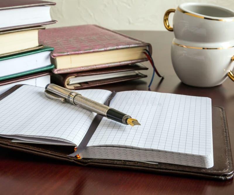 Livres, stylos, insigne, café photographie stock libre de droits