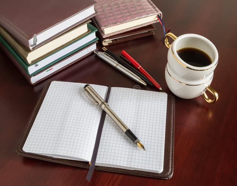 Livres, stylos, insigne, café photo stock