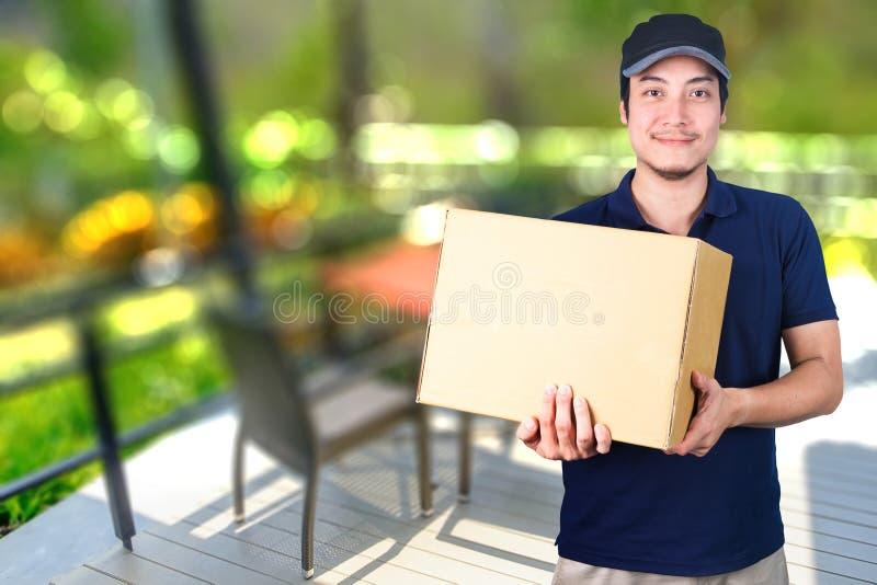 Livreur asiatique de sourire avec la boîte en carton à disposition se tenant dessus photographie stock libre de droits