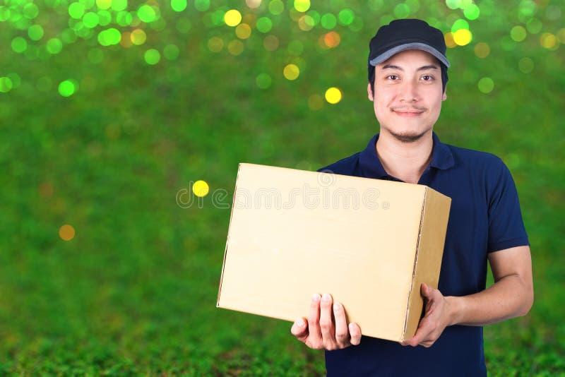 Livreur asiatique de sourire avec la boîte en carton à disposition se tenant dessus image libre de droits