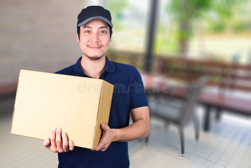 Livreur asiatique de sourire avec la boîte en carton à disposition se tenant dessus photo libre de droits