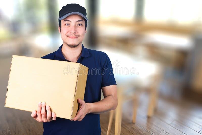 Livreur asiatique de sourire avec la boîte en carton à disposition tenant la recherche image stock