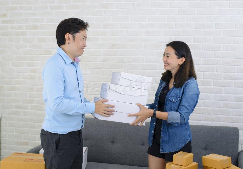 Livreur asiatique donnant la boîte à la fille attirante images stock