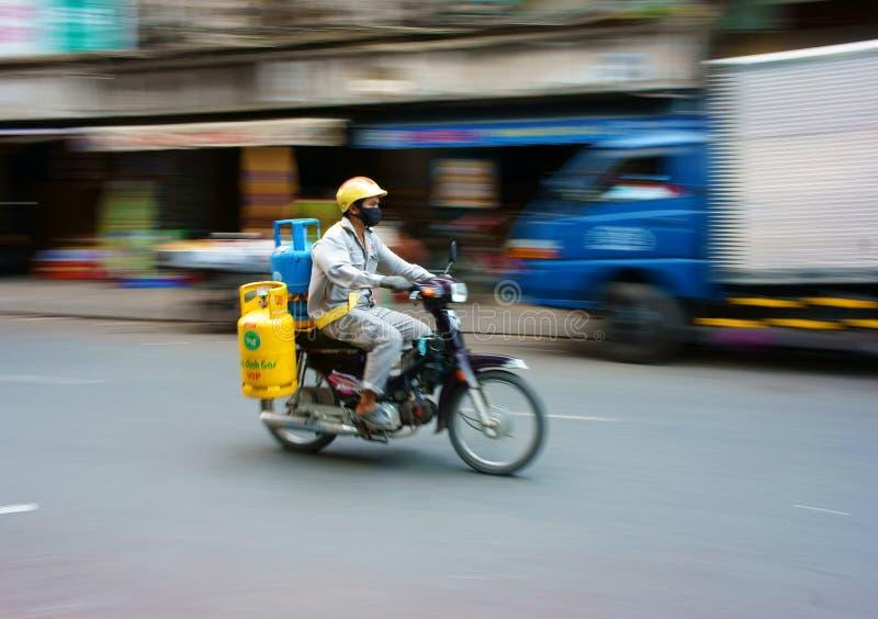 Livreur asiatique, réservoir de gaz de transport photo stock