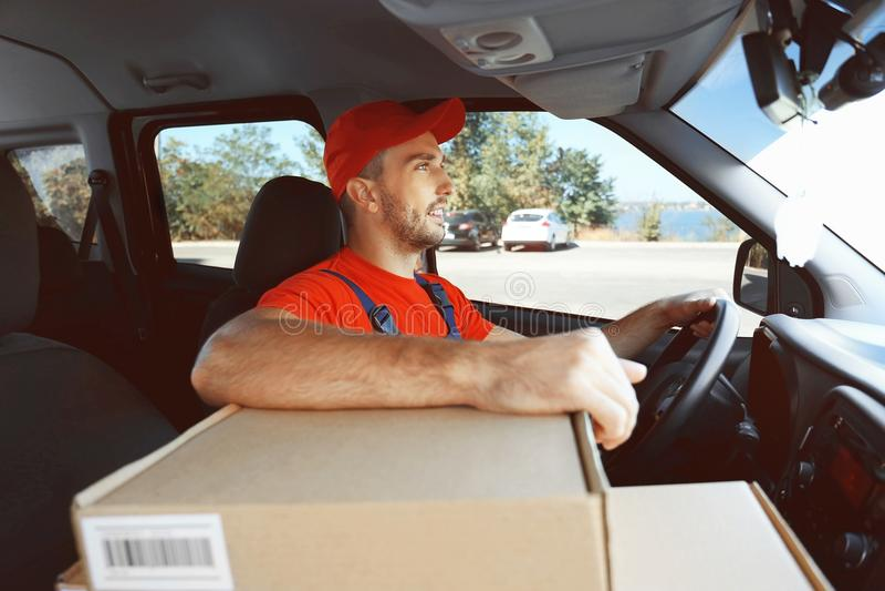 Livreur conduisant la voiture chargée photographie stock libre de droits
